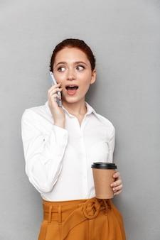 Ritratto di gioiosa redhead imprenditrice 20s in abbigliamento formale utilizza lo smartphone in ufficio e bere caffè da asporto dal bicchiere di plastica isolato su grigio