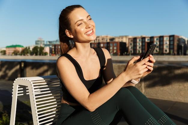 Ritratto di una donna allegra e sportiva che indossa una tuta sportiva che tiene in mano lo smartphone e si siede su una sedia mentre si allena in una strada cittadina