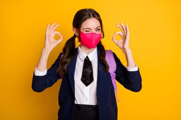Ritratto di gioiosa ragazza adolescente mostra ok segno ammiccamento ammiccante indossare maschera medica uniforme