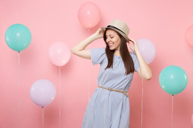 Ritratto di gioiosa giovane donna tenera con gli occhi chiusi in cappello estivo di paglia e vestito blu su sfondo rosa pastello con mongolfiere colorate. festa di compleanno persone sincere emozioni concetto.