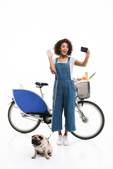 Ritratto di donna gioiosa che prende selfie ritratto su smartphone mentre si trova in piedi con il suo carlino e la bicicletta isolati su un muro bianco