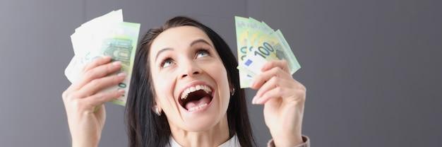 Ritratto di donna gioiosa che tiene le banconote in mano come vincere il concetto della lotteria