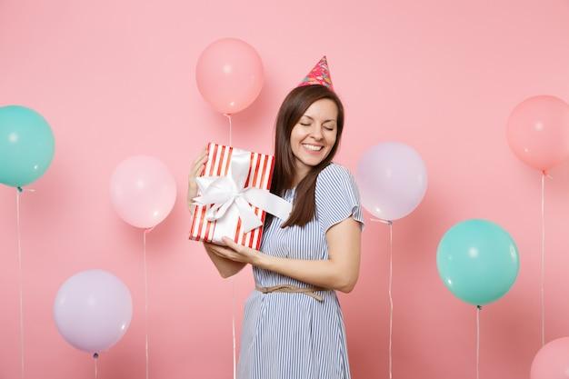 Ritratto di donna gioiosa con gli occhi chiusi in abito blu cappello di compleanno che tiene scatola rossa con regalo presente su sfondo rosa con palloncini colorati. festa di compleanno, persone sincere emozioni.