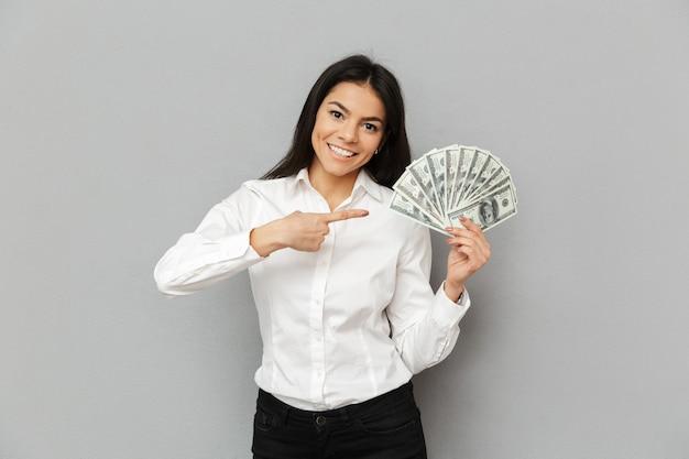 Ritratto di donna allegra con lunghi capelli castani indossando abiti da ufficio sorridente e puntando il dito su un sacco di dollari in mano, isolato sopra il muro grigio