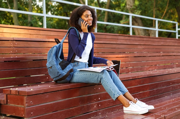 Ritratto di una gioiosa giovane ragazza africana con zaino parlando al cellulare mentre si riposa al parco, leggendo la rivista