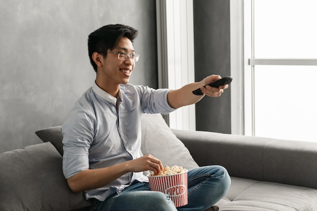 Ritratto di un giovane uomo asiatico allegro che tiene popcorn