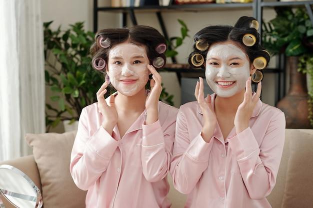 Ritratto di gioiose giovani belle donne che testano nuove maschere idratanti e purificanti, sono sedute sul divano in pigiama di seta e guardano la fotocamera