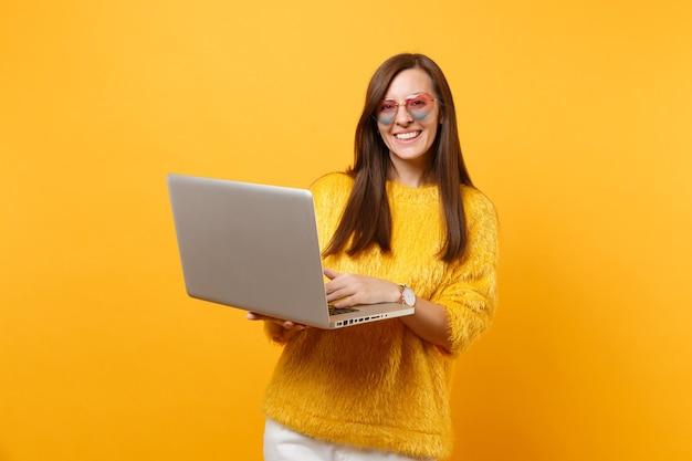 Ritratto di gioiosa giovane donna in maglione di pelliccia e occhiali a cuore che lavora su computer pc portatile isolato su sfondo giallo brillante. persone sincere emozioni, concetto di stile di vita. zona pubblicità.