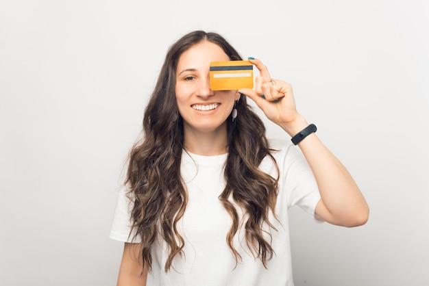 Ritratto di giovane donna allegra che sorride e copre gli occhi con la carta di credito credit