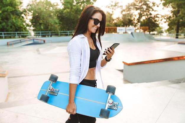 Ritratto di gioiosa giovane donna in streetwear sorridente e tenendo il cellulare mentre trasporta lo skateboard in park