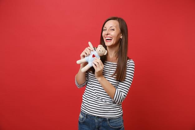 Ritratto di gioiosa giovane donna in abiti a righe che tiene e gioca con un peluche orsacchiotto