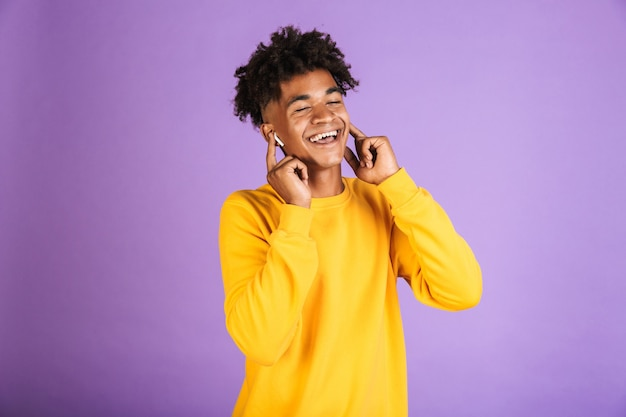 Ritratto di gioioso uomo afroamericano con elegante acconciatura afro sorridente, mentre si ascolta la musica tramite auricolare bluetooth, isolato su sfondo viola