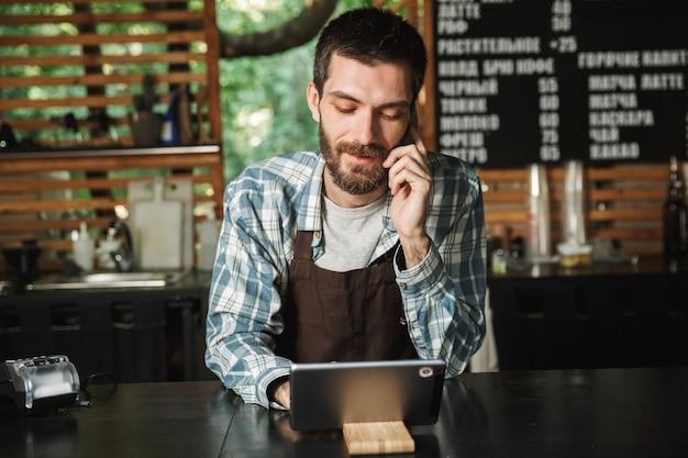 Ritratto di gioioso barista che indossa un grembiule utilizzando un computer tablet mentre si lavora in un caffè di strada o in un caffè all'aperto