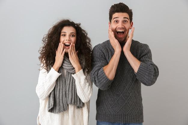 Ritratto di coppia gioiosa uomo e donna urlando e toccando il viso, isolato sopra il muro grigio