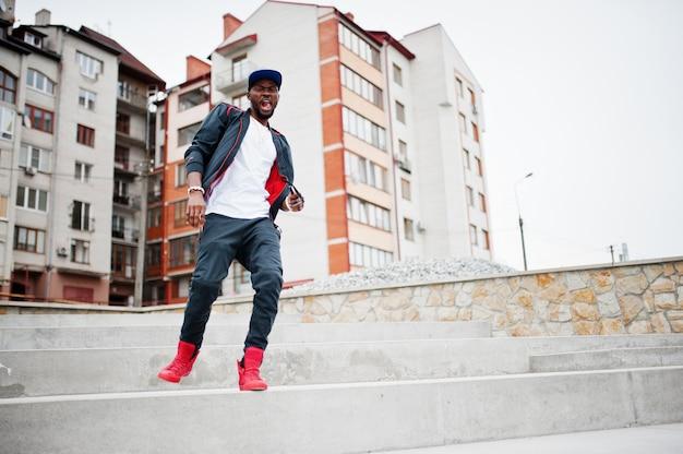Ritratto di saltare elegante uomo afroamericano su abiti sportivi, cappello e occhiali. moda da uomo emozione modello strada nera.