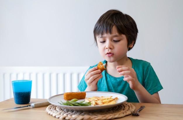 Ritratto del ragazzo del bambino che mangia bastoncino di pesce e patate fritte casalinghi per la cena di domenica a casa