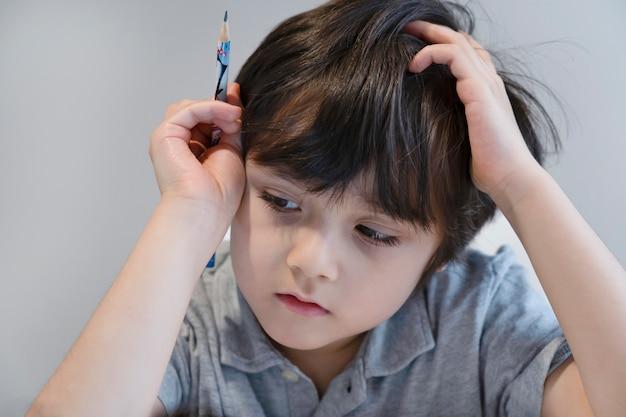 Ragazzo del bambino del ritratto che tiene la penna nera che si siede da solo e che guarda giù con la faccia annoiata, bambino solo che guarda d giù alla tavola con la faccia triste, bambino di cinque anni annoiato con i compiti della scuola, bambino viziato