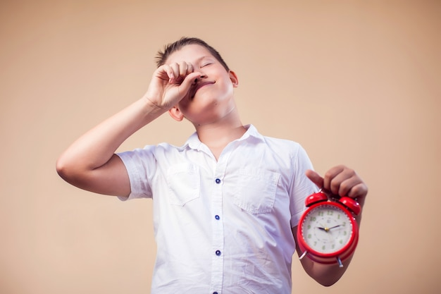 Ritratto del ragazzo del bambino che tiene sveglia rossa. concetto di gestione dell'infanzia e del tempo