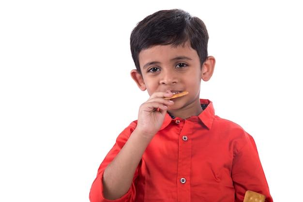 Ritratto di bambino che mangia un biscotto su sfondo bianco