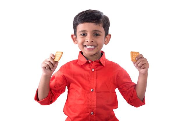 Ritratto di bambino che mangia un biscotto sul muro bianco