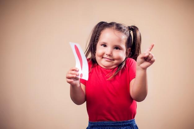 Ritratto della ragazza del bambino che tiene carta con punto esclamativo. concetto di educazione e bambini