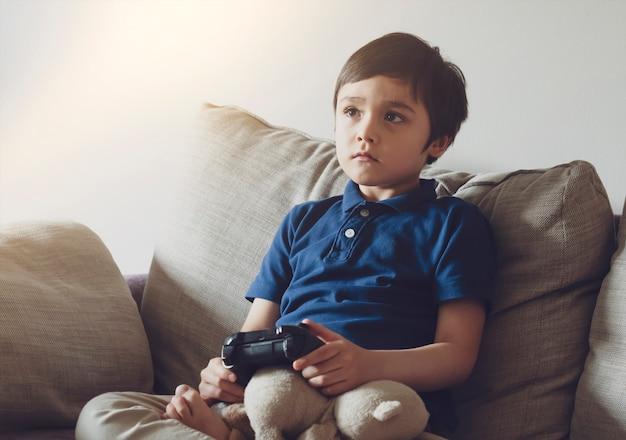 Ritratto del bambino che tiene videogioco o console di gioco. bambino che gioca online a casa mentre la scuola fuori.