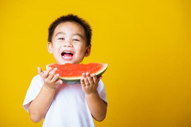 Il sorriso del ragazzino del bambino del ritratto tiene l'anguria tagliata fresca per mangiare