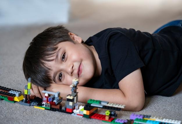 Ragazzo del ritratto che gioca i blocchi di plastica, ragazzo felice del bambino che si trova sul pavimento della moquette che bluide i suoi giocattoli colorati dei blocchi