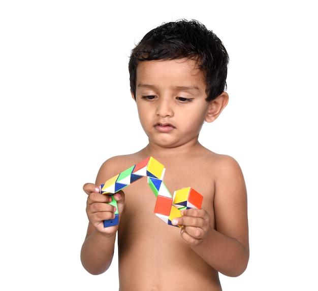 Ritratto di bambino che gioca con il giocattolo su uno sfondo bianco