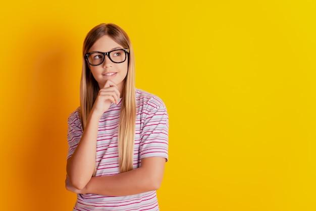Il ritratto del mento di tocco del bambino pensa che sembri uno spazio vuoto isolato su sfondo giallo