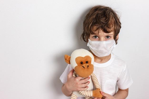 Ritratto di bambino che indossa maschera medica con scimmia giocattolo su bianco