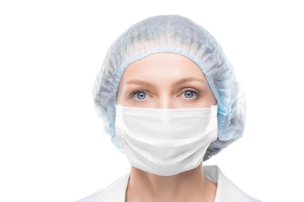 Ritratto di signora medico con gli occhi azzurri che indossa la maschera per il viso e cappuccio chirurgico