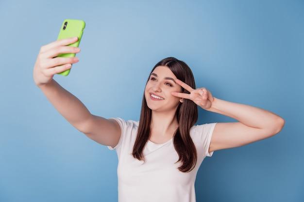 Il ritratto della signora tiene il tiro del telefono selfie mostra l'occhio della copertura del gesto di pace del v-sign su fondo blu
