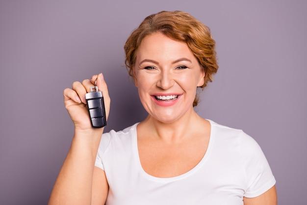 Ritratto di signora in maglietta bianca che tiene le chiavi della macchina isolate sulla porpora