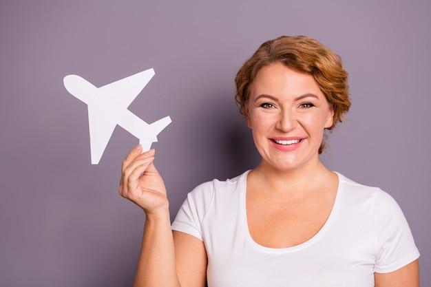 Ritratto di signora in t-shirt bianca che tiene aeroplano di carta isolato sulla porpora