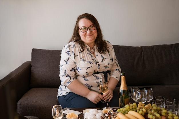 Ritratto di una grande donna in bicchieri con un bicchiere di vino seduto sul divano