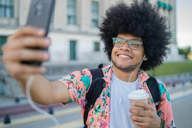 Ritratto di uomo latino che tiene una tazza di caffè e prendendo un selfie con il telefono cellulare stando in piedi all'aperto sulla strada. concetto urbano.
