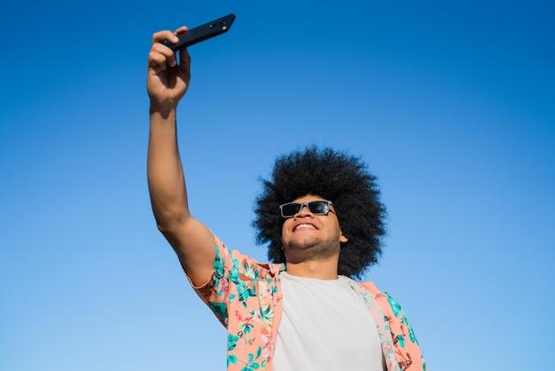 Ritratto di uomo latino prendendo un selfie con il suo telefono cellulare stando in piedi all'aperto sulla strada