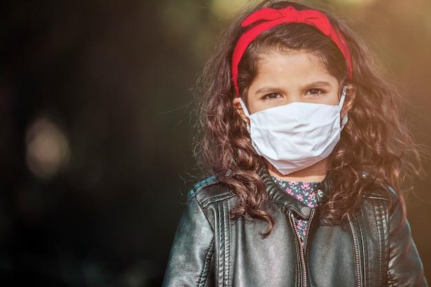 Ritratto di una giovane ragazza latina, che indossa una maschera ed esamina la macchina fotografica in un parco. ha un'espressione drammatica coronavirus e concetto di infanzia. immagine con copyspace