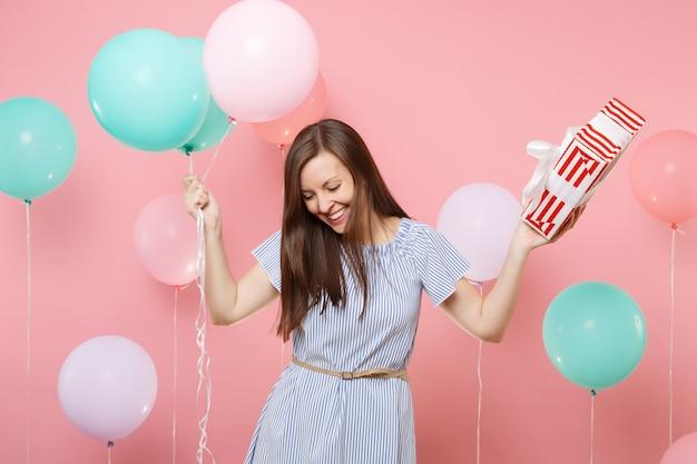 Ritratto di ridente donna attraente che indossa abito blu guardando in basso tenendo scatola rossa con regalo presente e palloncini d'aria colorati su sfondo rosa di tendenza brillante. concetto di festa di compleanno.