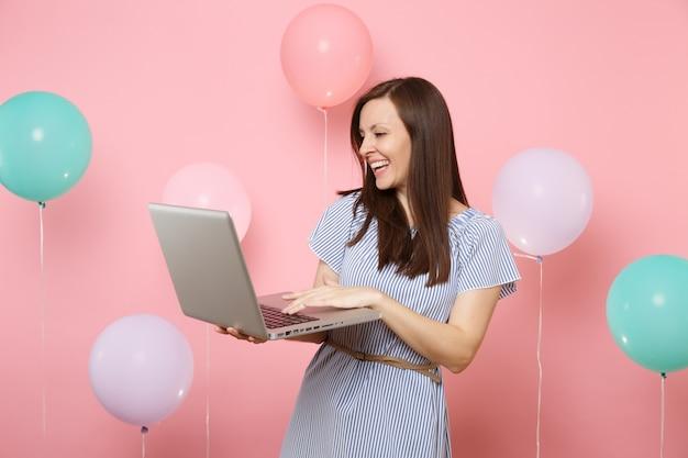 Ritratto di risata attraente giovane donna in abito blu che tiene utilizzando computer pc portatile su sfondo rosa pastello con mongolfiere colorate. festa di compleanno persone sincere emozioni concetto.