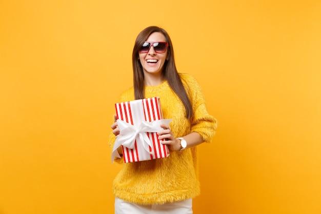 Ritratto di bella giovane donna ridente in occhiali rossi che tiene scatola rossa con regalo, presente isolato su sfondo giallo brillante. persone sincere emozioni, concetto di stile di vita. zona pubblicità.