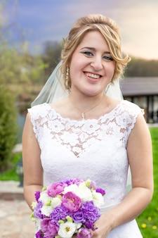 Ritratto della sposa bionda di risata che posa con il mazzo nuziale all'aperto