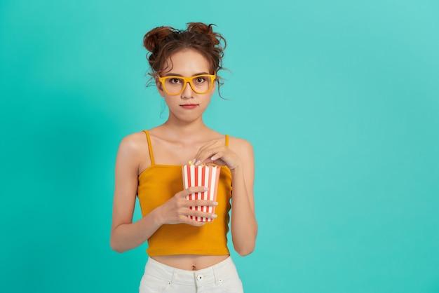 Ritratto di una ragazza che ride in abiti casual che tengono scatola di popcorn e che guarda l'obbiettivo isolato sopra luminoso