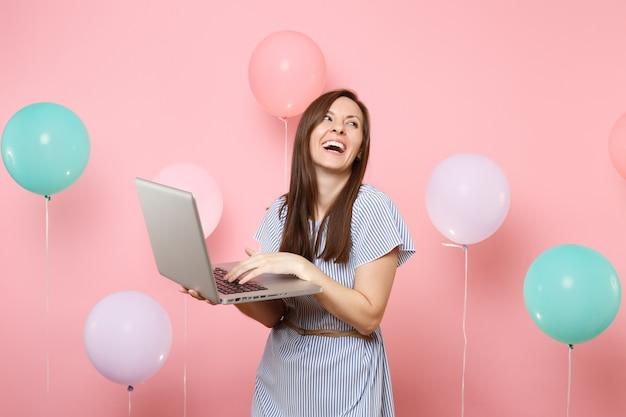 Ritratto di ridendo gioiosa giovane donna in abito blu che tiene utilizzando il computer pc portatile su sfondo rosa pastello con mongolfiere colorate. festa di compleanno persone sincere emozioni concetto.