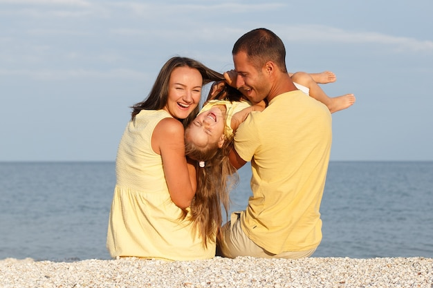 Ritratto di una bambina ridente in abiti gialli che corre in riva al mare