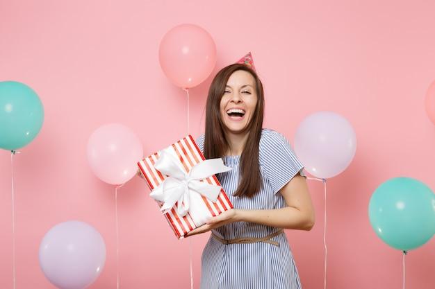 Ritratto di donna graziosa che ride in cappello di compleanno e vestito blu che tiene scatola rossa con regalo presente su sfondo rosa pastello con palloncini colorati. festa di compleanno, persone sincere emozioni.