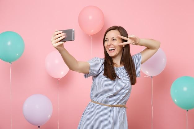 Ritratto di giovane donna ridente in abito blu che fa selfie sul telefono cellulare che mostra il segno di vittoria su sfondo rosa con mongolfiere colorate. festa di compleanno, concetto di emozioni sincere della gente.