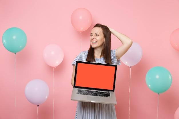 Ritratto di giovane donna ridente in abito blu che tiene il computer pc portatile con schermo vuoto vuoto aggrappato alla testa guardando da parte su sfondo rosa con mongolfiere colorate. festa di compleanno. Foto Premium