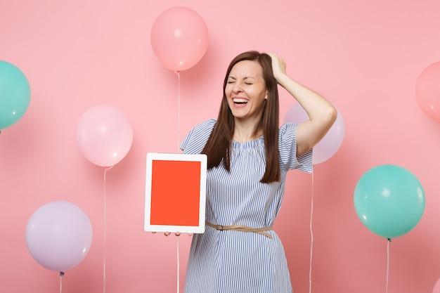 Ritratto di giovane donna che ride in abito blu che tiene computer tablet pc con schermo vuoto vuoto aggrappato alla testa su sfondo rosa pastello con mongolfiere colorate. concetto di festa di compleanno.